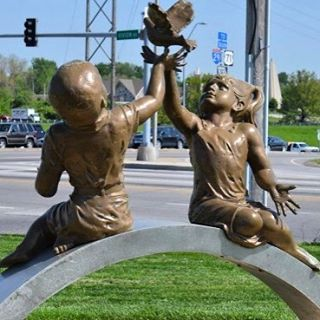 Our #WhatsThatWednesday image is of the Bridge of Friendship statue #KCParks #WTW Artist:  Yao XilaiDedicated:  October 28, 2000Medium:  Stainless steel, bronzeDescription: A sculpture of a boy and girl sitting on a small bridge releasing a dove.  It signifies the friendship between Kansas City and it's sister city of Xi'an, China.The sculptor, Yao Xilai, was commissioned by Kansas City resident Bob Chien.  The first commission of this sculpture was for Xi'an in 1992 and its sister was placed in Kansas City in 2000.  Chien is a major proponent of the sister city relationship between Kansas City and Xi'an and was an official delegate when the Sister City Agreement between the two cities.It is located on the northwest side of the intersection of Vivion Road and Oak Trafficway on the corner opposite the Northland Fountain.