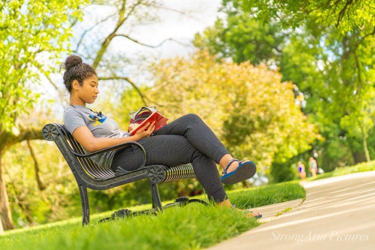 girl on park bench reading