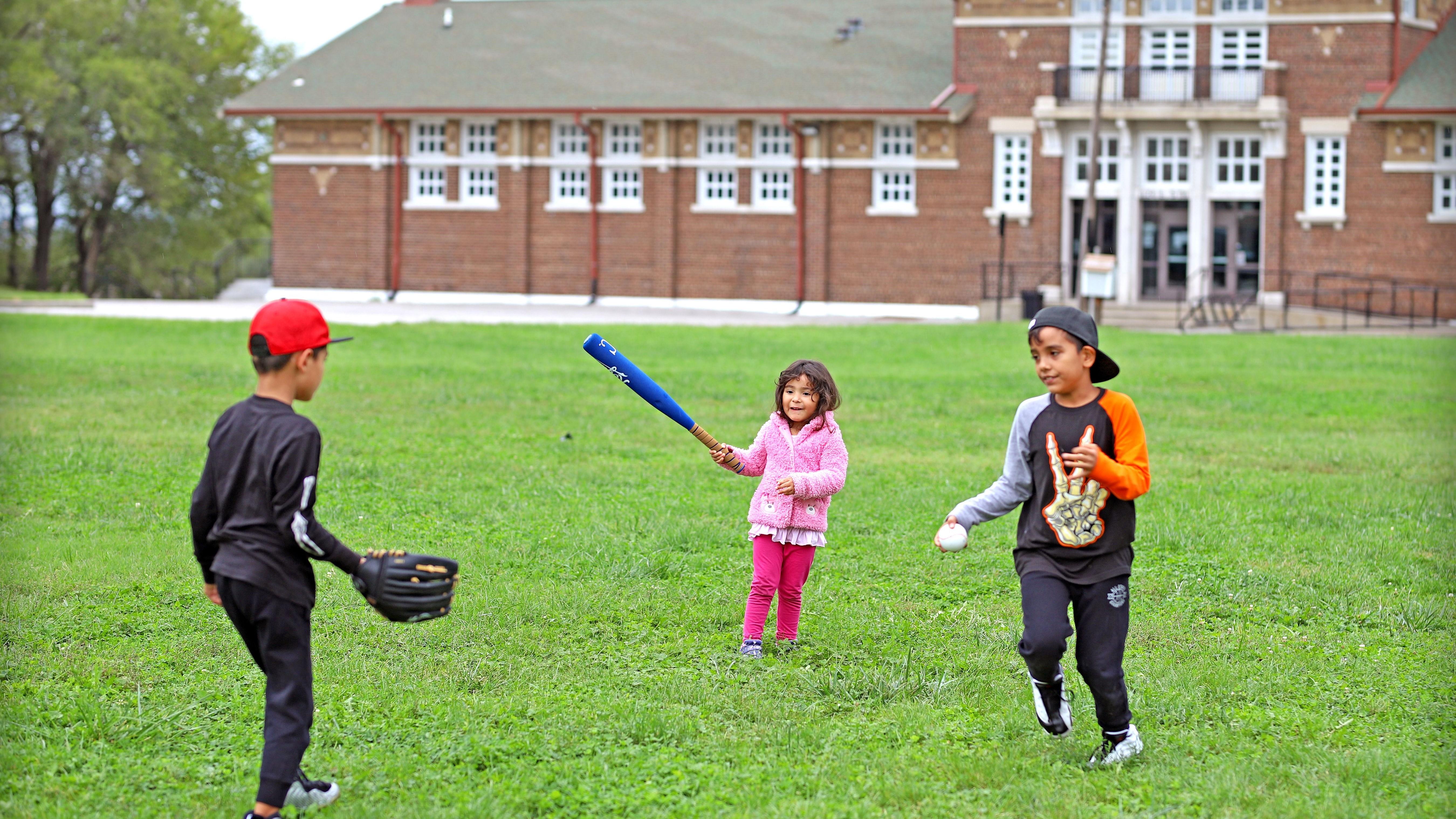 Kids playing baseball infront of Garrison Square