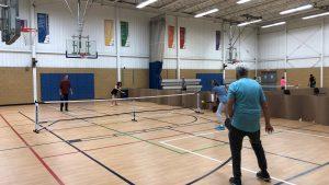 People playing Tennis in Indoor Court