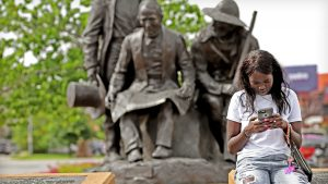 Girl on her phone infront of pioneers statue