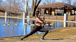 Girl exercising infront of the pond with ducks