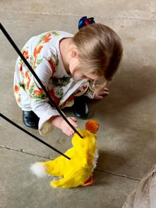 girl playing with toy duck