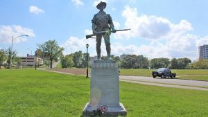 Individual with a gun statue