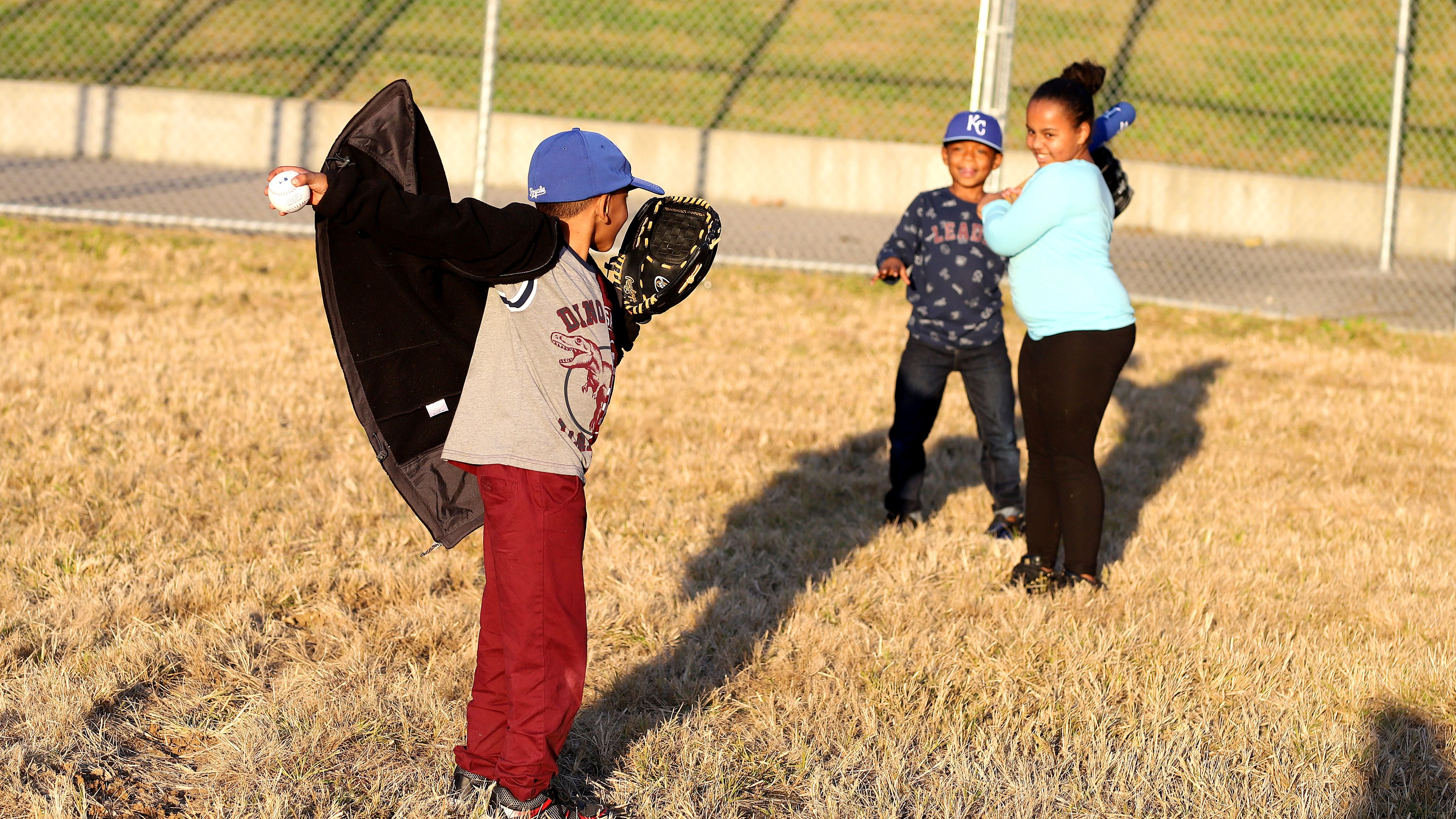 Kids playing baseball wearing KC gear