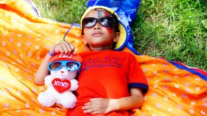 Kid dressed in bright color with a Teddy Bear laying in the sun