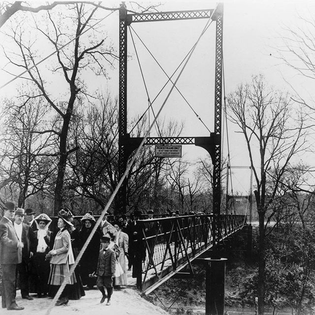 "{Throwback Thursday} Built in 1907 by the Midland Bridge Company, this bridge was originally meant to span a nearly inaccessible area of dense underbrush to connect Swope Park's Grand Entrance with a proposed athletic field. It was affectionately known as the ""Swinging Bridge"" because of its tendency to sway from side to side with foot traffic. The bridge was renovated in the 1990s.  It is 227 feet long and is suspended approximately 94 feet above the Blue River.  It is now part of the Zoo's African Exhibit. #KCParks #TBT #throwbackthursday"