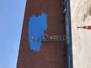 Girl painting on KC wall