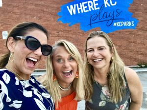 people taking a picture infront of KC parks wall art