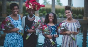 Girls Dressed up holding flowers in the park