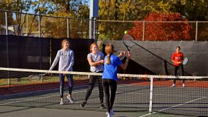 Kids playing tennis in the fall